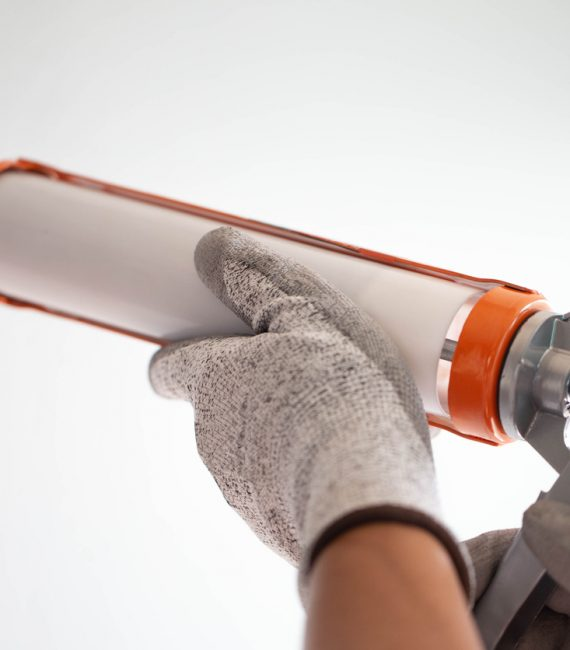 Men's hand uses silicone adhesive with a glue gun to repair worn windows.