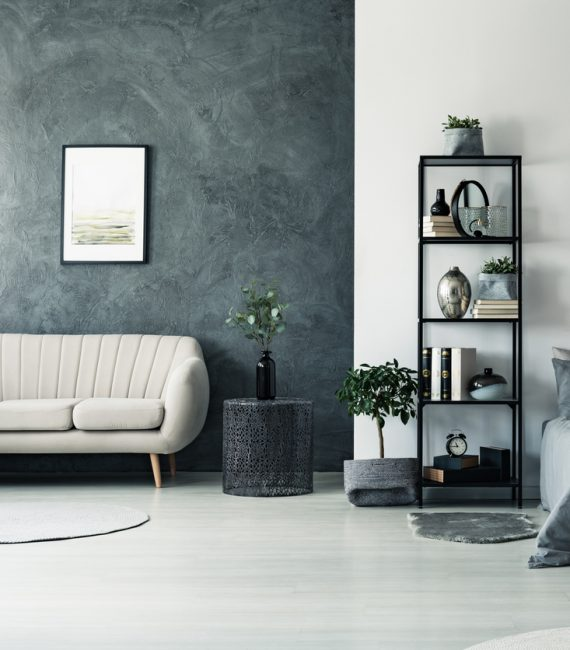 Elegant beige sofa standing by a black wall underneath a painting in a house interior